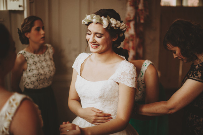 Bride smiling holding her stomach with her eyes closed wearing a flower crown made by whichgoose