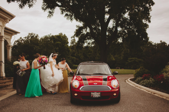Bridesmaids in all different pantone colors helping bride to mini car