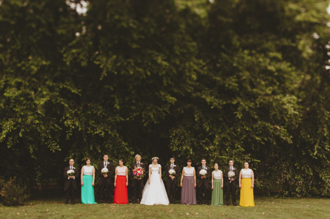 Bridal party standing in a line with bridesmaids wearing mismatched bright skirts and groomsmen in formal morning coats