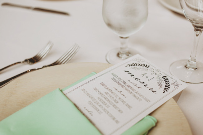 Wedding menus by wedding paper divas wrapped in mint green napkin