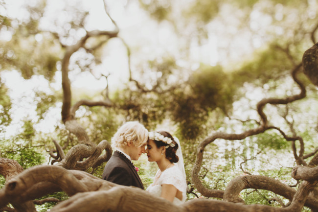 Bride and groom head to head surrounded by tree branches