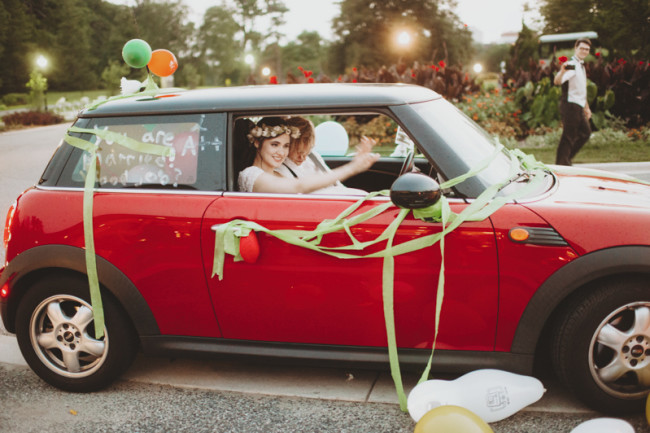 Bride and groom driving off in red mini covered in ribbons