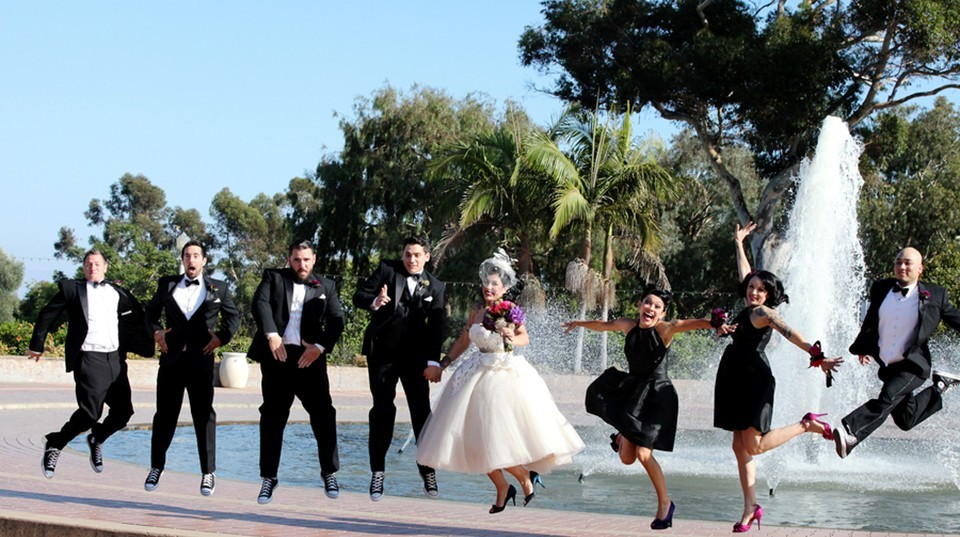 Bride and groom with bridal party jumping in front of San Diego Fountian