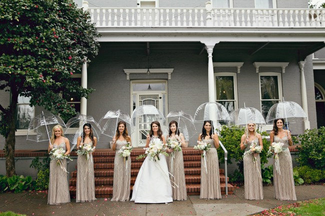 A bride with her bridesmaids lined up holding clear umbrellas. Give clear umbrellas for bridesmaids gifts