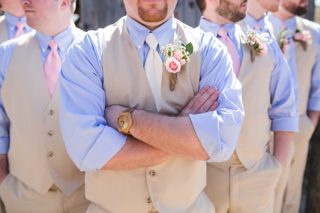 groom standing with groomsmen wearing tan vests and pants and pink ties