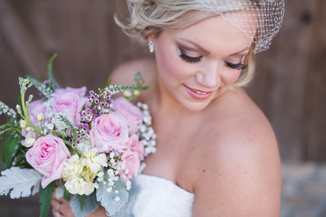 Bride wearing a french netting birdcage veil and holding a bouquet created by Pam's Posies Florist
