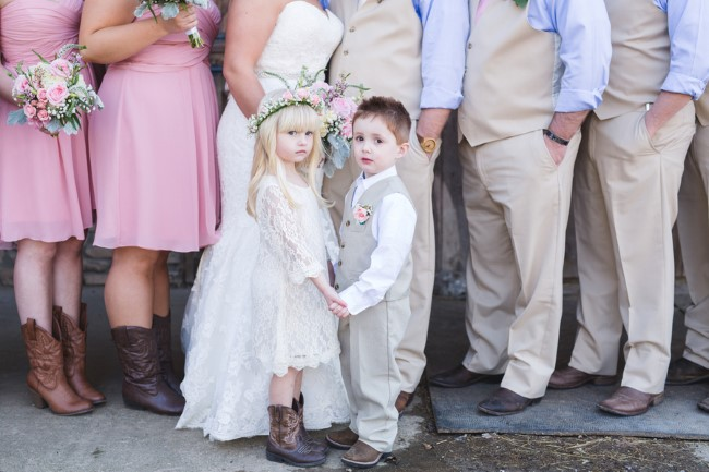 Flower girl wearing a floral crown and cowboy boots holding hands with ring bearer