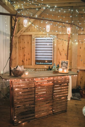 Rustic wedding reception bar with mini white lights