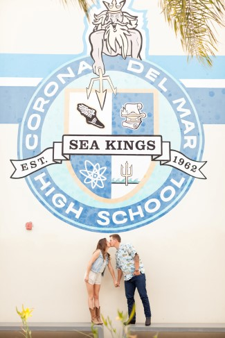 Couple kissing under the corona del mar high school sign