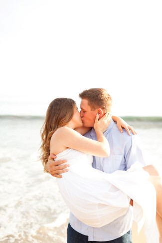 Guy carrying girl in his arms standing on the beach while they kiss