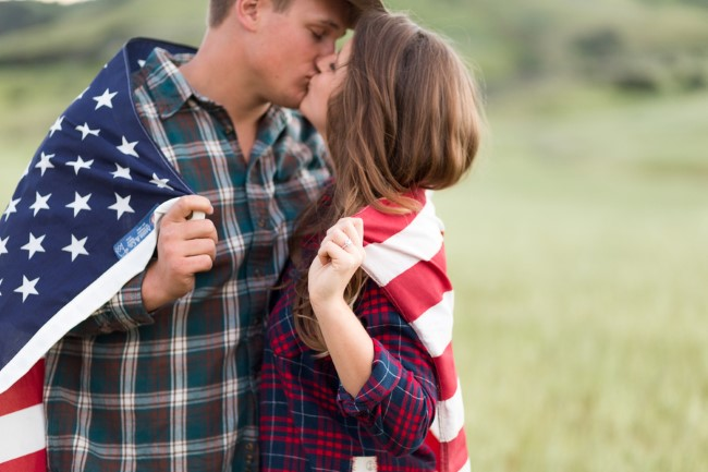 Couple kissing in a field with an american flag wrapped around them