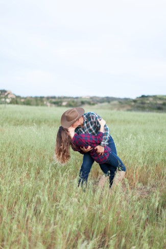 Engagement session in an open field with rustic plaid shirts