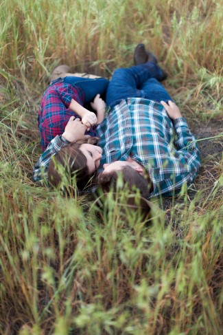 Couple laying in a grass field with plaid shirts