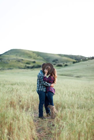 Couple standing in a field kissing behind a cowboy hat