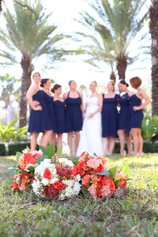 bride standing with bridesmaids in navy dresses and red and white bouquets