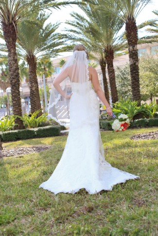 Bride wearing a fit to flair dress and a fingertip length veil with lace edging