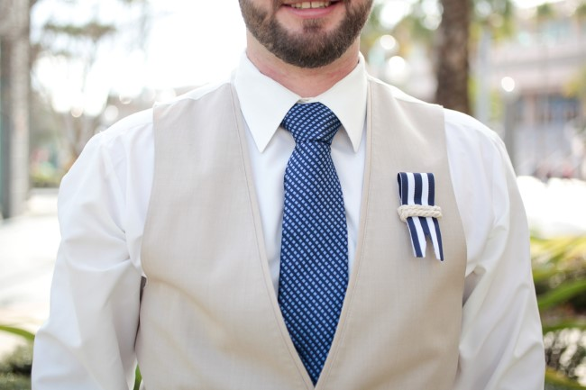 groom wearing beige vest and nautical themed boutonniere