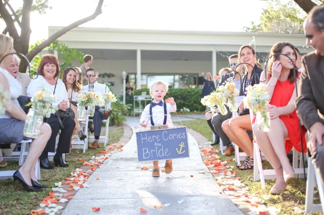 Ring bearer walking with a nautical themed chalkboard sign saying the bride is coming