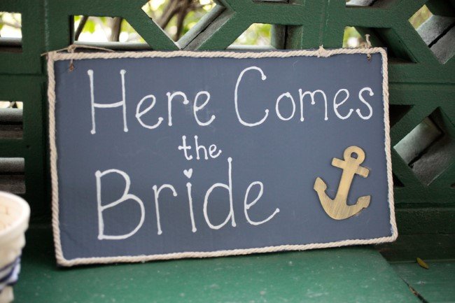 Nautical chalkboard sign that says here comes the bride