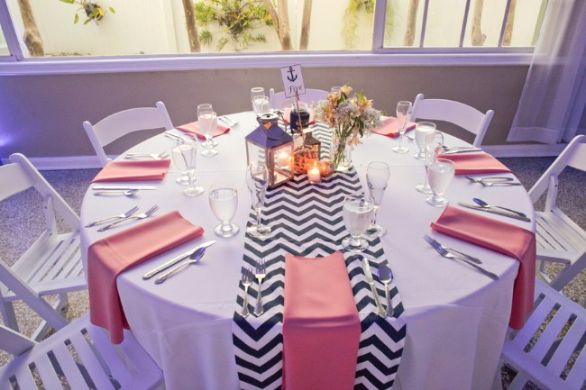 pink napkins with a blue and white chevron patterned table runner for nautical wedding reception