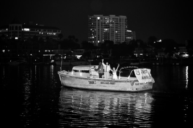 Bride and groom leaving their wedding on a motor boat
