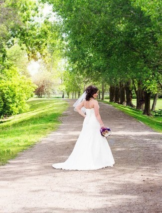 bride walks down gravel path at Lion's Lodge