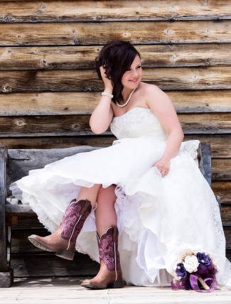 bride in cowboy boots sitting on wood bench