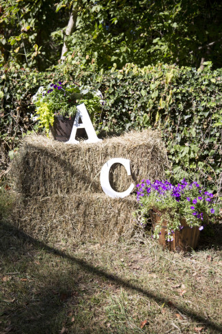 Rustic outdoor wedding decor using hay stacks and large white letters