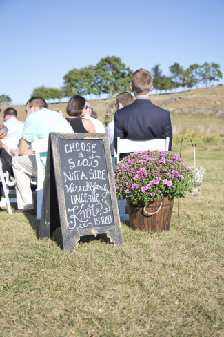 Sandwich board for wedding guest seating arrangements telling them to choose a seat not a side