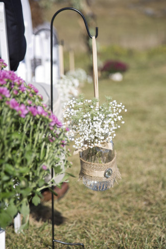 Wedding aisle decor using baby's breath in a jar wrapped in burlap