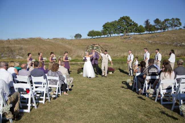 Outdoor wedding ceremony in field at Cloverdale Barn