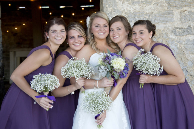 Bride standing with bridesmaids wearing purple dresses and holding baby's breath bouquets