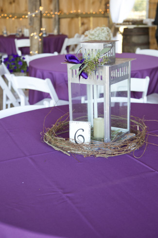 Wedding reception table with purple table cloth and lantern for a center piece