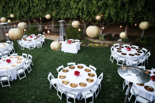 Backyard wedding reception with gold lanterns and chargers