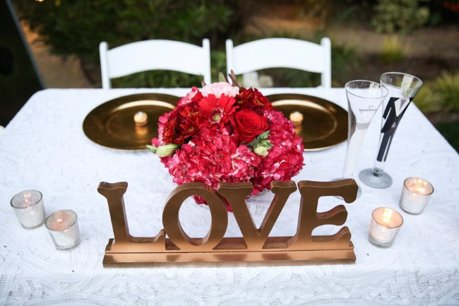 Gold and red themed wedding reception bride and grooms table