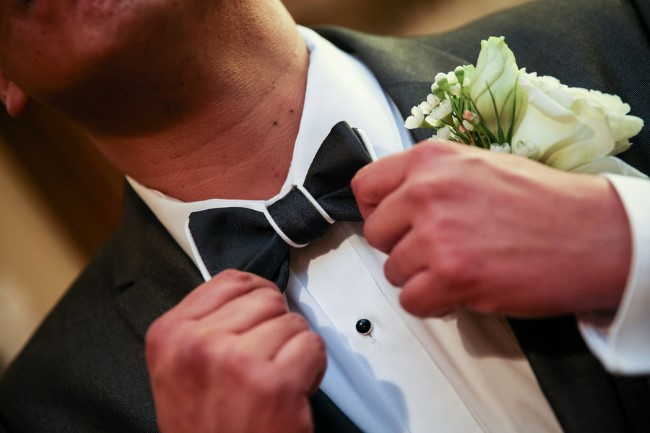 Groom wearing a suit and bow tie from men's warehouse