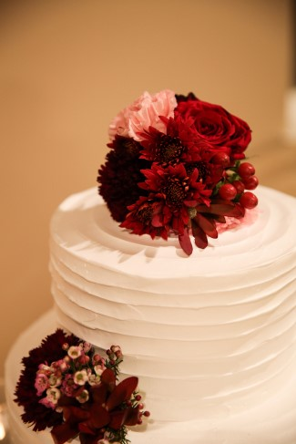 2 tier round white wedding cake with red floral cake toppers