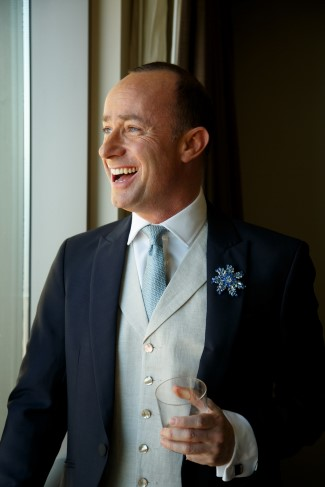 Laughing groom in bespoke suit with blue necktie and sparkle boutonniere