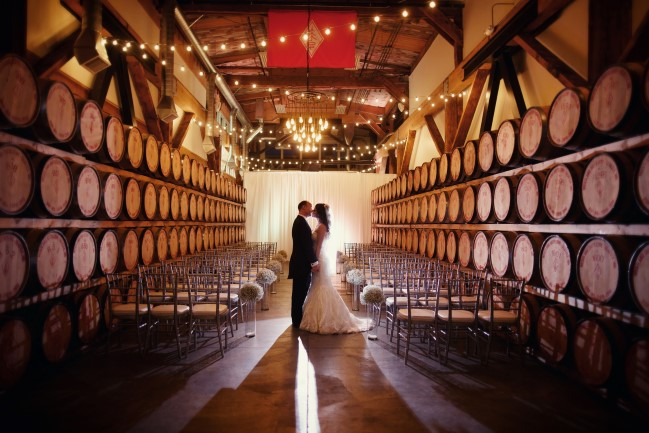 Bride and groom kiss in barrel room of Westland Distillery