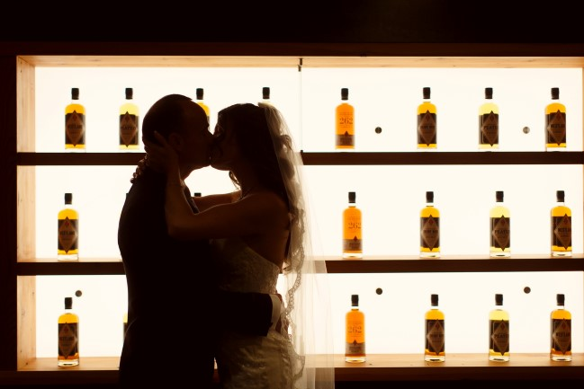 bride and groom kiss with backlit whiskey bottles at the bar