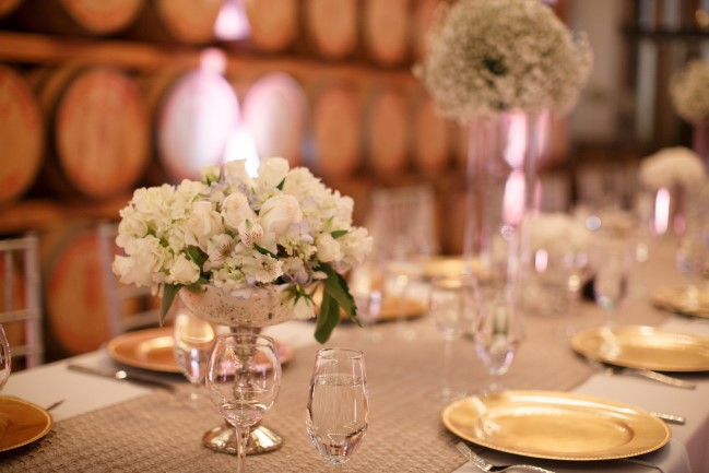 white floral centerpiece and gold chargers