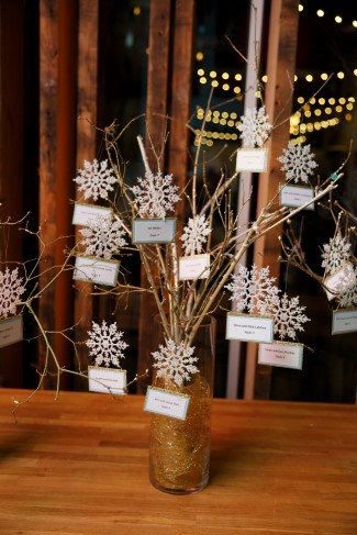 twigs with fake snowflakes and name tags hanging