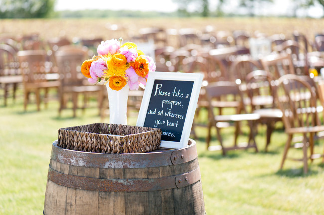 Wedding ceremony decor using wine barrel and orange, yellow and pink yellow billy balls, football mums and spider mums