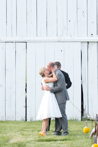 Bride and groom kissing during outdoor ceremony captured by Tamara Jaros Photography