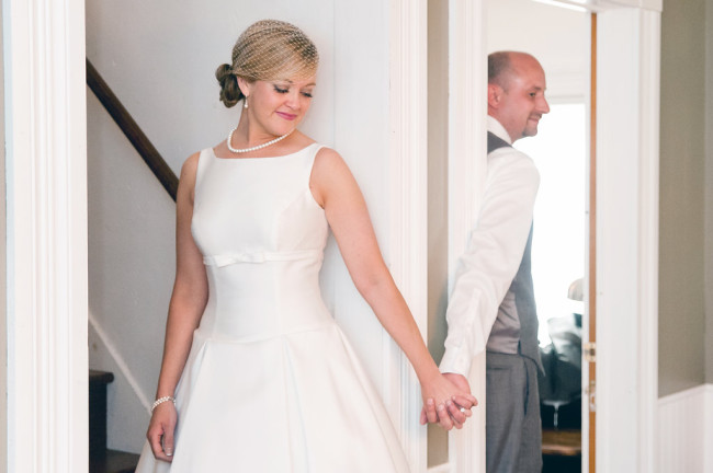 Bride wearing 50's style gown holding hands with groom for first look captured by Tamara Jaros Photography