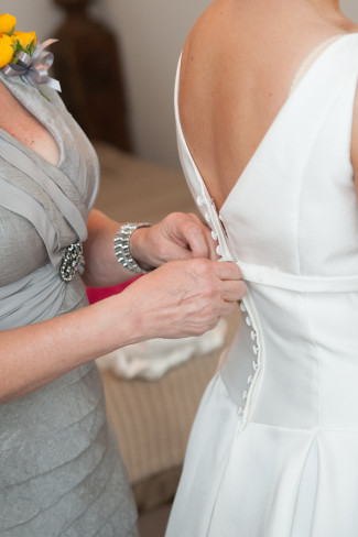 Mother of the bride buttoning bride's gown by Moonlight Bridal