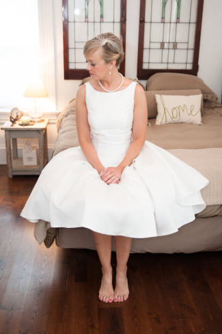 bride sitting on bed wearing a Audrey Hepburn-inspired tea length dress by Moonlight Bridal