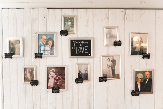 A wall of family photos for wedding reception