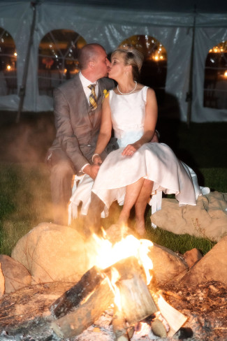 Bride and groom kissing in front of camp fire during outdoor reception