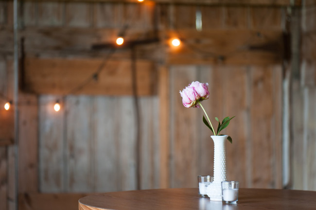 Pink rose in a white milk glass vase for wedding reception center piece